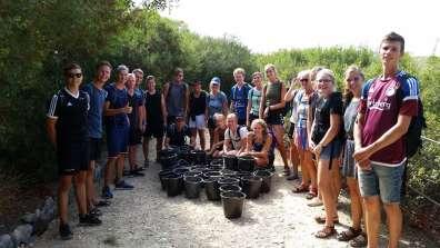 קבוצת מתנדבים ולפניה הדליים שהעלו מתחתית מפעל המים